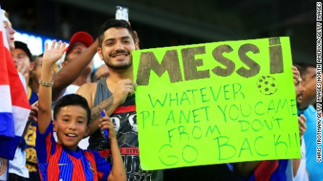 Barcelona fans pose with a sign for Lionel Messi in Miami. The Argentine could be returning sooner than they think.