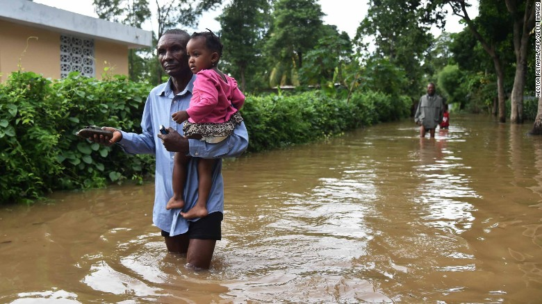A man carries a child through a flooded street in Fort-Liberte, Haiti, on Friday, September 8. Hurricane Irma has barreled through the Caribbean, leaving catastrophic damage to islands in its path.