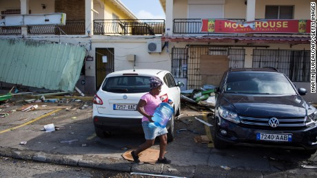 A woman carries a container of water on a street in Marigot, on the island of St. Martin, September 10.