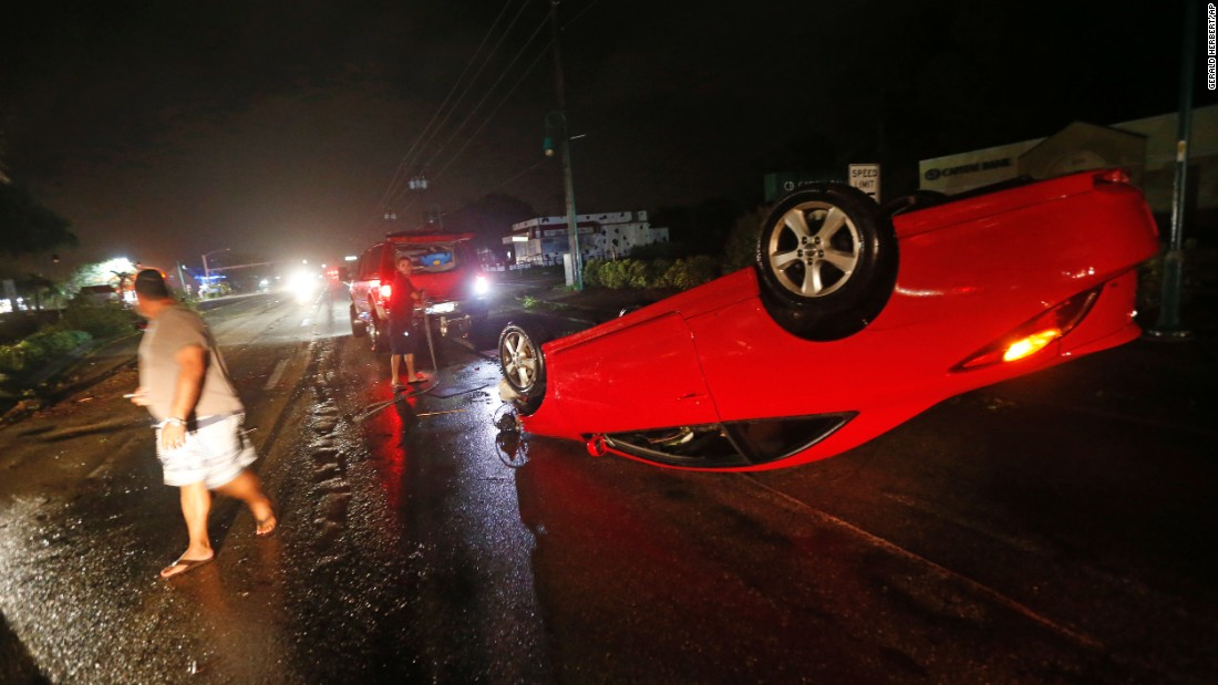 People in Cape Coral, Florida, tend to a car that flipped over during Hurricane Irma on Sunday, September 10.