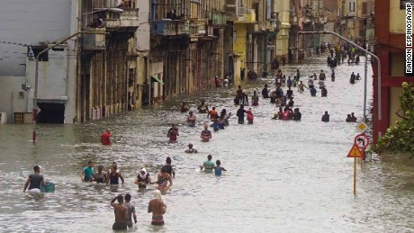 People move through flooded streets in Havana after the passage of Hurricane Irma, in Cuba, Sunday, Sept. 10, 2017. The powerful storm ripped roofs off houses, collapsed buildings and flooded hundreds of miles of coastline after cutting a trail of destruction across the Caribbean. Cuban officials warned residents to watch for even more flooding over the next few days. (AP Photo/Ramon Espinosa)