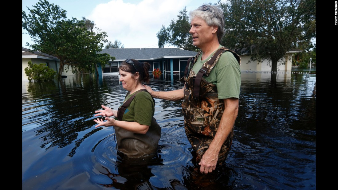 Kelly McClenthen and her boyfriend, Daniel Harrison, walk through floodwaters in Bonita Springs, Florida, on Monday, September 11. Hurricane Irma was downgraded to a tropical storm Monday, but its heavy winds and rain still pose a threat as it plows into Georgia and other parts of the Deep South.