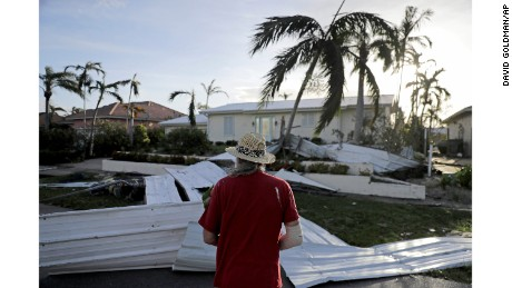 A roof is strewn across a home's lawn as Rick Freedman checks his neighbor's damage from Hurricane Irma in Marco Island, Fla., Monday, Sept. 11, 2017. (AP Photo/David Goldman)