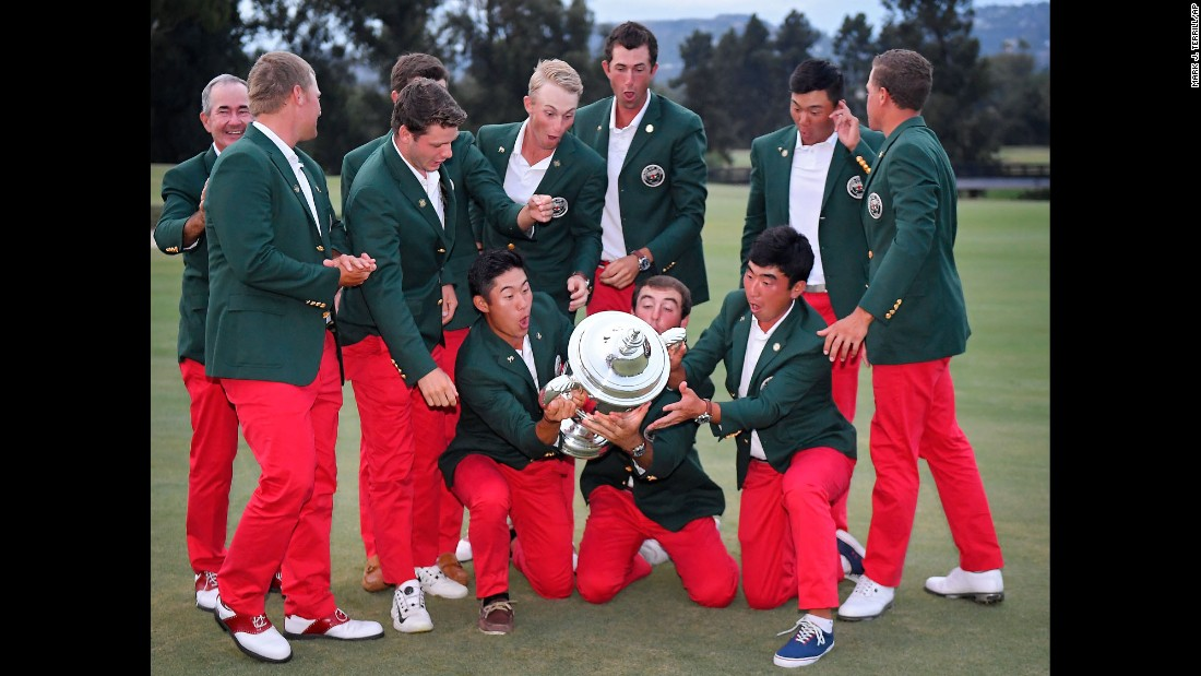 The US amateur golf team nearly drops the Walker Cup trophy after defeating Great Britain and Ireland on Sunday, September 10.