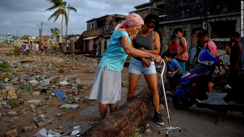 People make their way through debris in the Cojimar neighborhood of Havana.