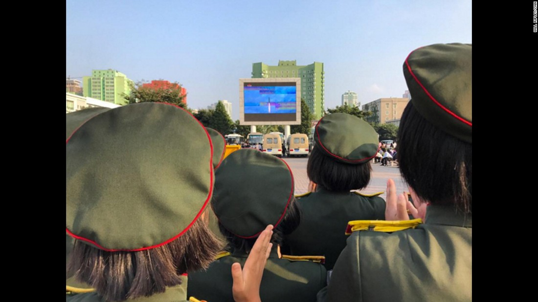 The crowd applauds as North Korean TV airs footage of their latest missile launch outside Pyongyang Station on August 30, 2017.