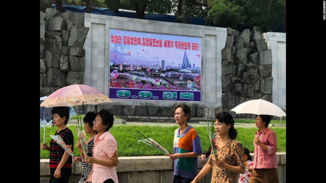 "Pyongyang residents walk past a poster marking the 69th DPRK Foundation Day on September 9. It reads ""Let the entire world look up to the great Kim Il Sung nation and Kim Jong Il Korea."""