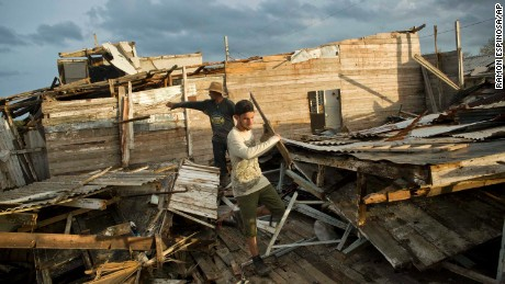People salvage material from the remains of a house in Isabela de Sagua, Cuba, on September 11.