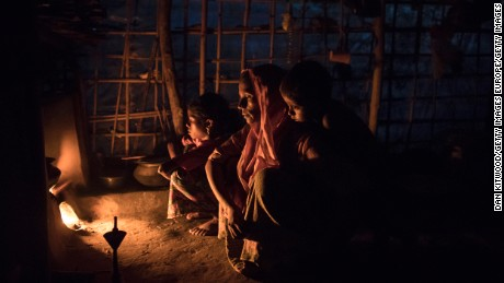 Rohingya Muslims who have been living in Bangladesh for more than a year sit by a fire at a shelter.