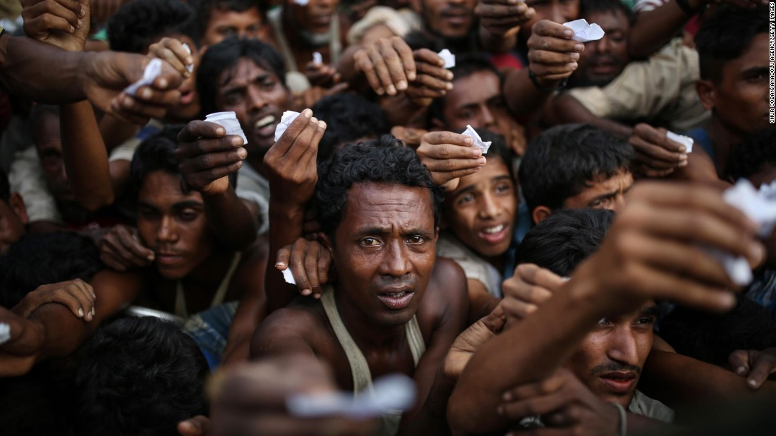 Rohingya men reach out for relief supplies at a refugee camp in Bangladesh on September 9.