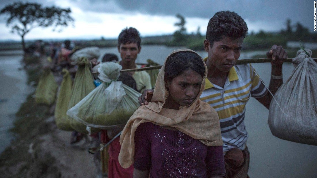 Rohingya refugees walk across paddy fields after crossing the border in Gundum, Bangladesh, on Saturday, September 9.