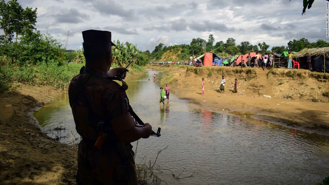 A Bangladeshi border guard orders Rohingya refugees to return to the Myanmar side of a small canal on Tuesday, August 29. Bangladesh has been struggling to cope with the influx of refugees.