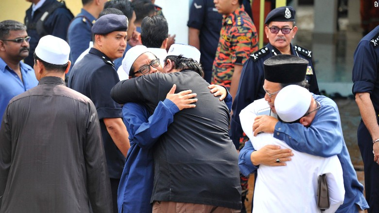 People console each other outside an Islamic religious school following the fire.