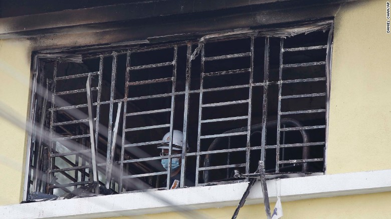 A forensic police officer investigates burnt windows at an Islamic religious school following the fire.