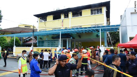 Police and rescue personnel work at an Islamic religious school cordoned off after a fire on the outskirts of Kuala Lumpur  Thursday, Sept. 14.