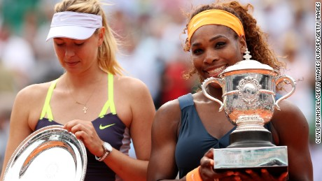 PARIS, FRANCE - JUNE 08:  Serena Williams of United States of America lifts the Coupe Suzanne Lenglen next to Maria Sharapova of Russia after victory in the Women's Singles Final match during day fourteen of French Open at Roland Garros on June 8, 2013 in Paris, France.  (Photo by Clive Brunskill/Getty Images)
