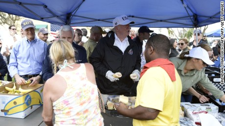 President Donald Trump, with Florida Gov. Rick Scott, left, Vice President Mike Pence, second left, and first lady Melania Trump, helps serve food to people affected by Hurricane Irma in Naples, Florida, on Thursday.