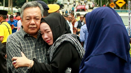 Nik Azlan Nik Abdul Kadir (L), father of one of the victims comforts his wife outside the school in Kuala Lumpur on September 14.