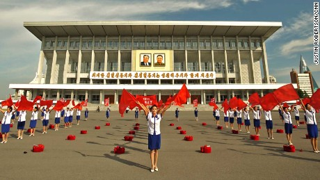 Women hold flags outside a building in the North Korean capital of Pyongyang.