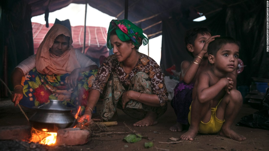 A Rohingya family cooks rice in a makeshift tent on September 15 in Tankhali, Bangladesh.