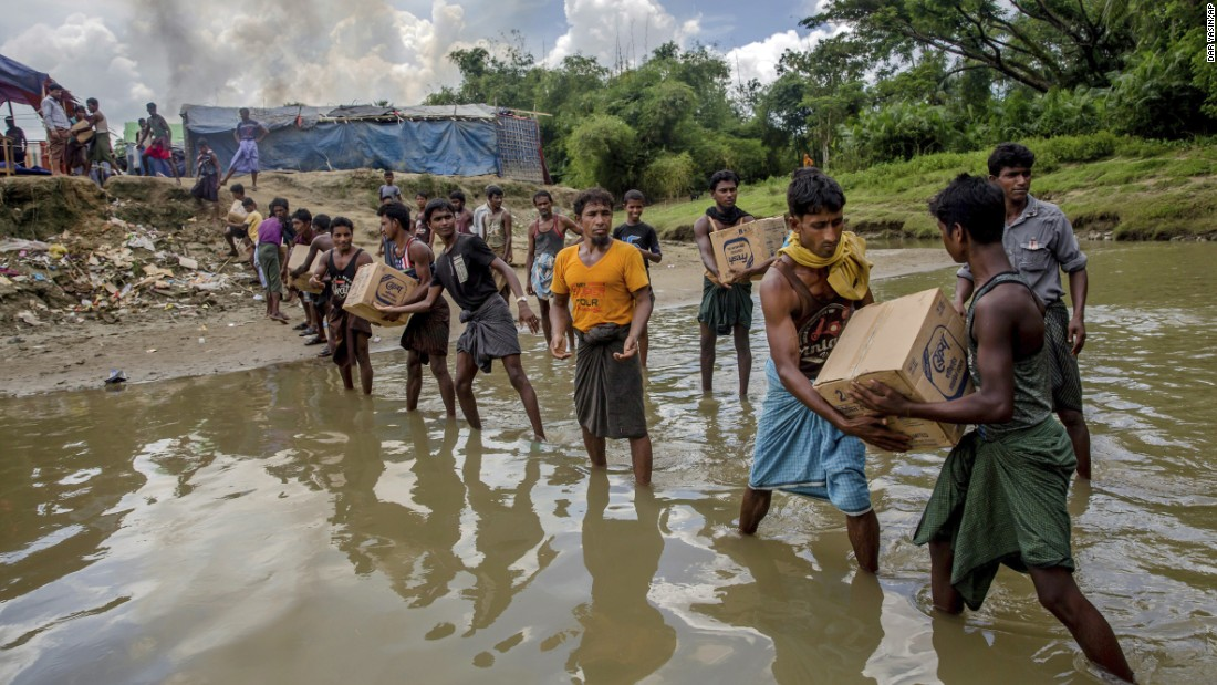 Refugees carry food items near the border to set up a refugee camp in Tombru, Bangladesh, on September 15.