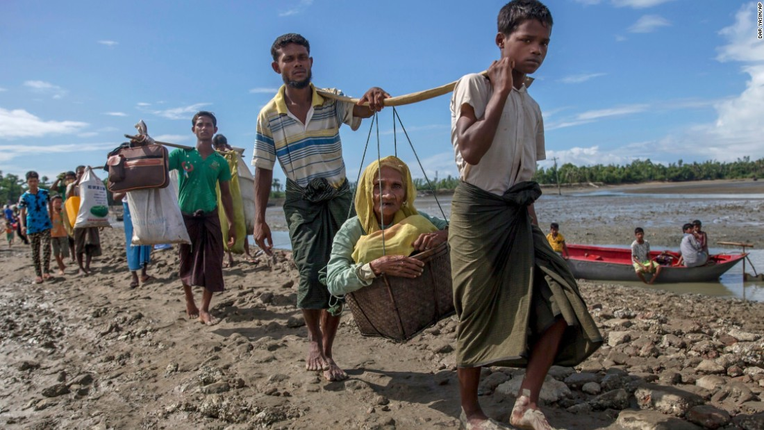 Rohingya refugees, who crossed from Myanmar into Bangladesh, carry an elderly woman as they walk toward a refugee camp in Shah Porir Dwip on September 14.