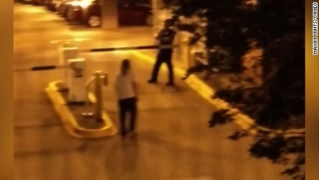 A still image taken from cellphone video shows Schultz, in the white shirt, walking toward an officer.