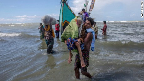 A Rohingya Muslim man walks to shore carrying an elderly woman after they arrived on a boat from Myanmar to Bangladesh.