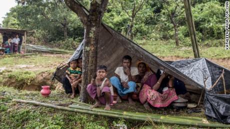 Refugees huddle together under scraps of tarpaulin and plastic.