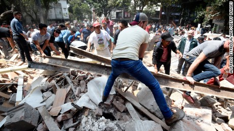 People remove debris off a building that collapsed after an earthquake rattled Mexico City.