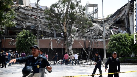 Police officers cordon the area off after a building collapsed during a quake in Mexico City on September 19. A powerful earthquake shook Mexico City, causing panic among the megalopolis' 20 million inhabitants on the 32nd anniversary of a devastating 1985 quake.