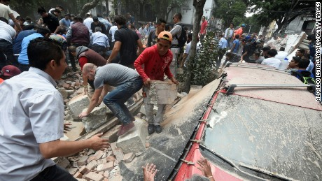 People remove debris of a building which collapsed after an earthquake rattled Mexico City on September 19.