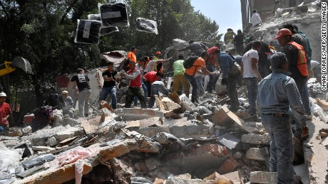 People remove debris of a collapsed building looking for possible victims after an earthquake rattled Mexico City on September 19.