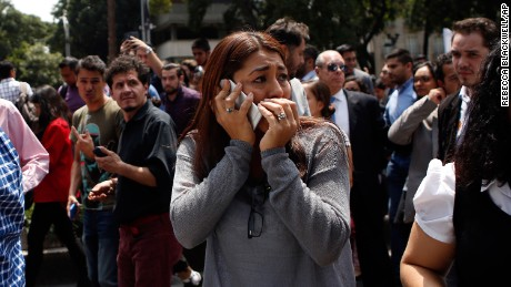 A woman speaks on her cell phone as people evacuated from an office building gather on Reforma Avenue after an earthquake in Mexico City, on September 19.