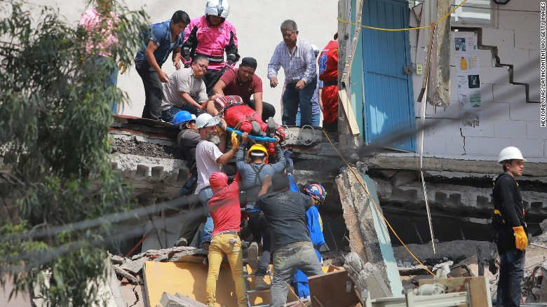 Rescuers and residents carry a woman to safety.