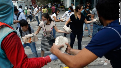 Volunteers pick up the rubble from a building that collapsed during an earthquake in the Condesa neighborhood of Mexico City on September 19.