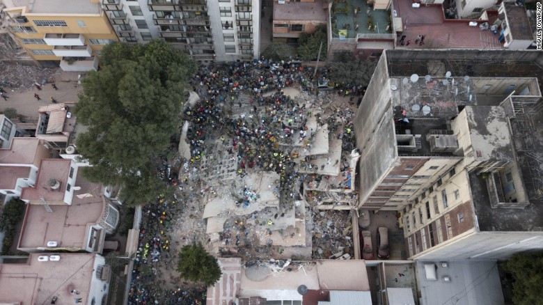 Rescue workers and volunteers search for survivors from a collapsed building in Mexico City