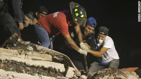 Rescue workers and volunteers search a building that collapsed after an earthquake in the Colonia Del Valle neighborhood of Mexico City, Tuesday, Sept. 19, 2017. A magnitude 7.1 earthquake has stunned central Mexico, killing at least more than 100 people as buildings collapsed in plumes of dust. Thousands fled into the streets in panic, and many stayed to help rescue those trapped. (AP Photo/Miguel Tovar)