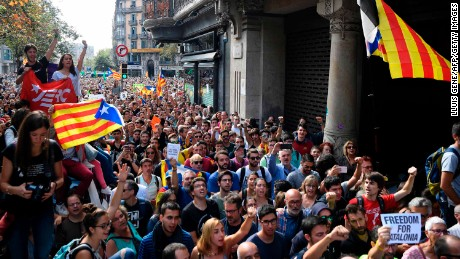 People holding  'Esteladas' (Catalan pro-independence flags) attend a protest in front of the Economy headquarters of Catalonia's regional government in Barcelona on September 20, 2017, during a search by Spain's Guardia Civil police.