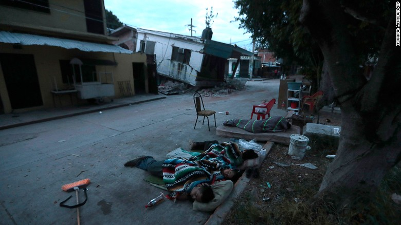 People sleep on the street next to damaged homes in Jojutla on September 20.