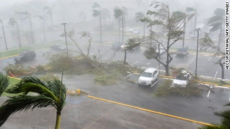 "Trees are toppled in a parking lot at Roberto Clemente Coliseum in San Juan, Puerto Rico, on September 20, 2017, during the passage of the Hurricane Maria. Maria made landfall on Puerto Rico on Wednesday, pummeling the US territory after already killing at least two people on its passage through the Caribbean. The US National Hurricane Center warned of ""large and destructive waves"" as Maria came ashore near Yabucoa on the southeast coast. / AFP PHOTO / HECTOR RETAMAL        (Photo credit should read HECTOR RETAMAL/AFP/Getty Images)"