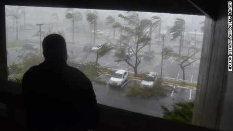 "A man looks as trees are toppled in a parking lot at Roberto Clemente Coliseum in San Juan, Puerto Rico, on September 20, 2017, during the passage of the Hurricane Maria. Maria made landfall on Puerto Rico on Wednesday, pummeling the US territory after already killing at least two people on its passage through the Caribbean. The US National Hurricane Center warned of ""large and destructive waves"" as Maria came ashore near Yabucoa on the southeast coast. / AFP PHOTO / HECTOR RETAMAL        (Photo credit should read HECTOR RETAMAL/AFP/Getty Images)"