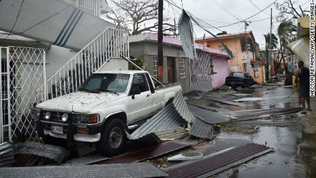Residents of San Juan, Puerto Rico, deal with damages to their homes on September 20, 2017, as Hurricane Maria batters the island.  Maria slammed into Puerto Rico on Wednesday, cutting power on most of the US territory as terrified residents hunkered down in the face of the island's worst storm in living memory. After leaving a deadly trail of destruction on a string of smaller Caribbean islands, Maria made landfall on Puerto Rico's southeast coast around daybreak, packing winds of around 150mph (240kph).  / AFP PHOTO / Hector RETAMAL        (Photo credit should read HECTOR RETAMAL/AFP/Getty Images)