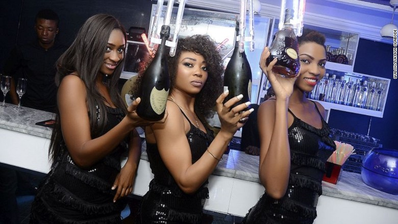 Partygoers pose with premium drinks in Quilox nightclub, Lagos.