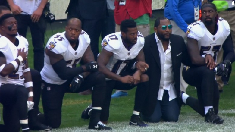 Retired Ravens linebacker Ray Lewis, in a sportcoat, joined his former team during Sunday's protest.