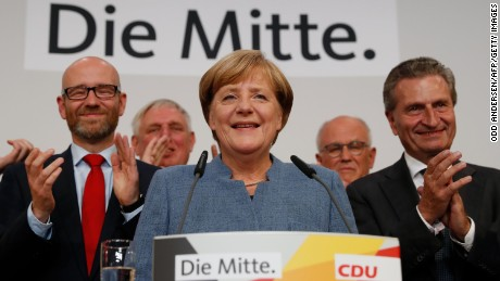 German Chancellor and CDU party leader Angela Merkel (C) addresses supporters after exit poll results were broadcasted on public television at an election night event at the party's headquarters in Berlin during the general election on September 24, 2017.