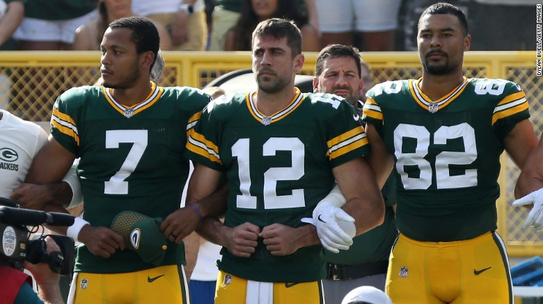 Green Bay Packers players, including quarterback Aaron Rodgers, stand with arms locked during the national anthem before their game against the Cincinnati Bengals.