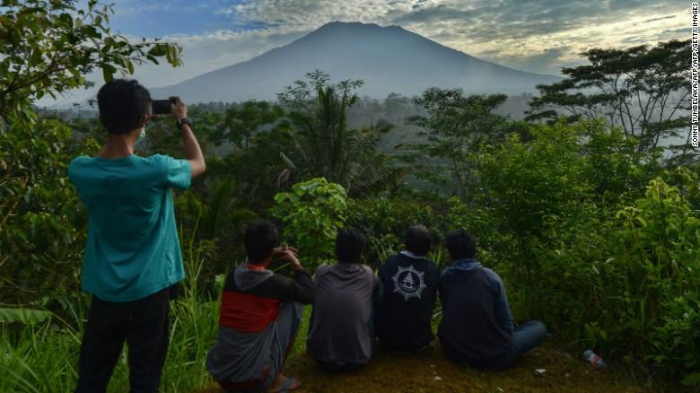 People look at Mount Agung in Karangasem on the Indonesian resort island of Bali on September 24, 2017.