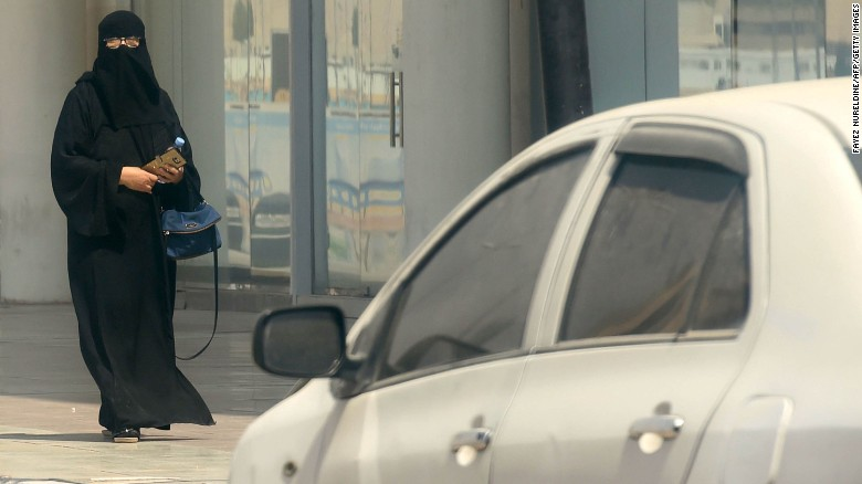 A Saudi woman walks near car down a street in the Saudi capital Riyadh on September 27, 2017.