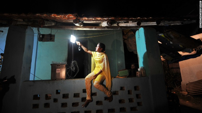 A girl switches on a light powered by solar energy in the village of Morabandar on Elephanta Island, off the coast of Mumbai.